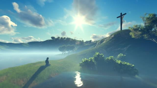 frau an jesus kreuz gegen schöne morgensonne beten - kreuz religiöser gegenstand stock-videos und b-roll-filmmaterial