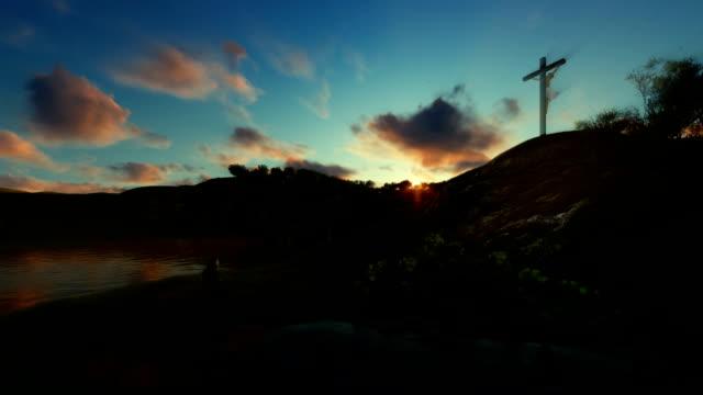 Woman praying at Jesus cross against beautiful sunset video