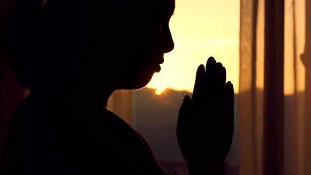 woman praying at sunset - armonia video stock e b–roll