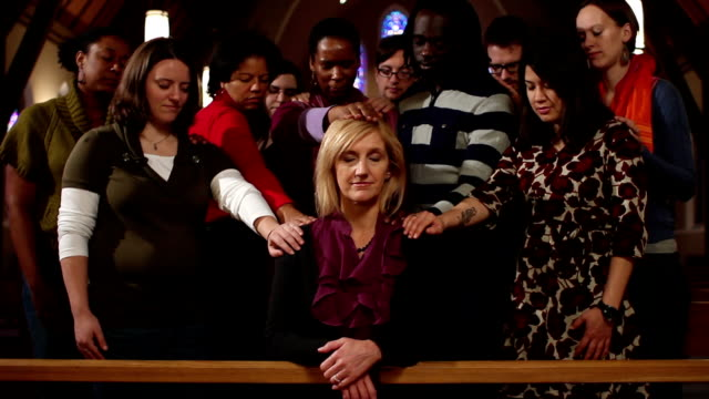 Woman praying with community laying hands on her video