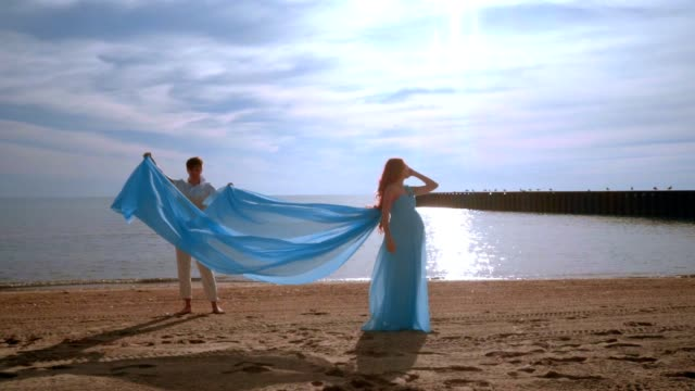 Woman pregnant on beach sea. Pregnant woman in blue dress flying on wind