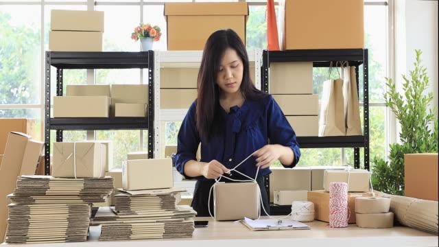 kvinna förbereder paket post för skicka till kund. - skicka datormeddelande bildbanksvideor och videomaterial från bakom kulisserna