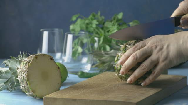 Woman prepared pineapple for Spicy pineapple jalapeno mezcalita or margarita for Cinco de Mayo video