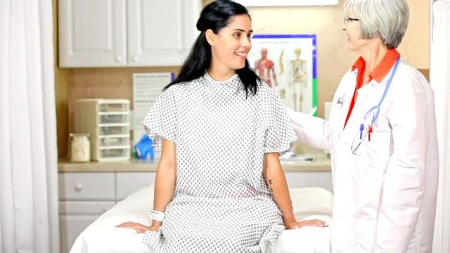 stockvideo's en b-roll-footage met vrouw bereidt voor borst examen, mammogram op doctor's office of ziekenhuis. - breast cancer
