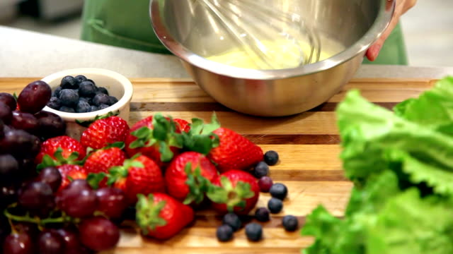 Woman prepares fruit dessert in home kitchen. video