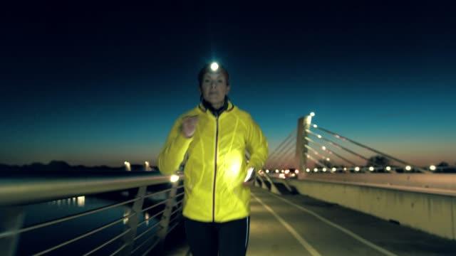 slo-mo-frau bereitet eine smartphone zum abspielen von musik beim joggen über die brücke - einzelne frau über 30 stock-videos und b-roll-filmmaterial
