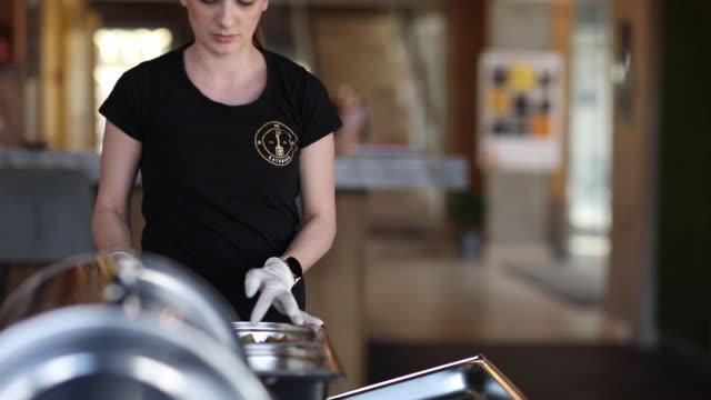 Woman preparing food table before buffet