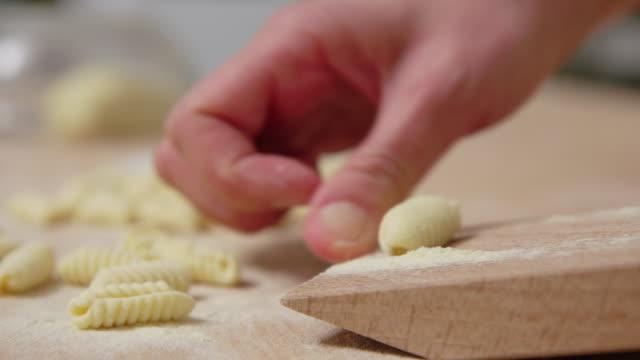 Woman preparing pasta on gnocchi board