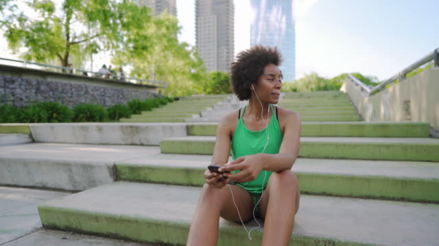 Woman preparing right music for running while taking a break