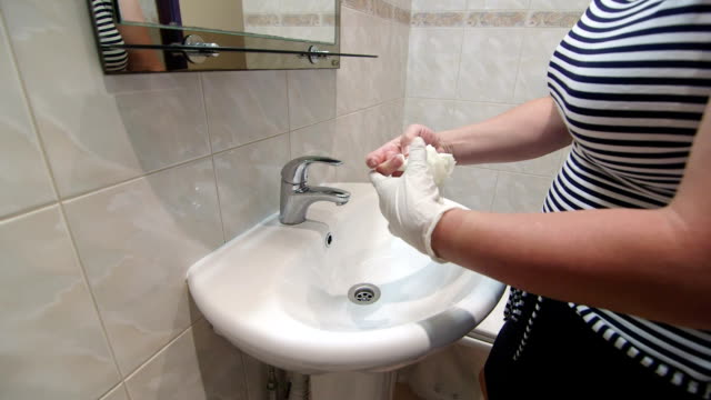 Woman preparing to clean bathroom putting on rubber cleaning gloves video