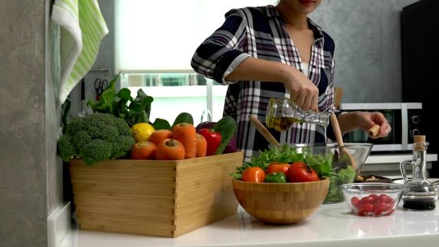채식주의 믹스 샐러드 사용 올리브 오일과 발사믹 식초 드레싱을 준비 하는 여 자가 건강 한 라이프 스타일 영상 - 식초 스톡 비디오 및 b-롤 화면