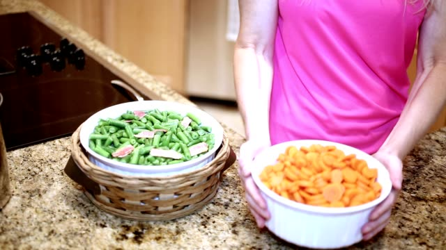 Woman preparing vegetables in home kitchen. video