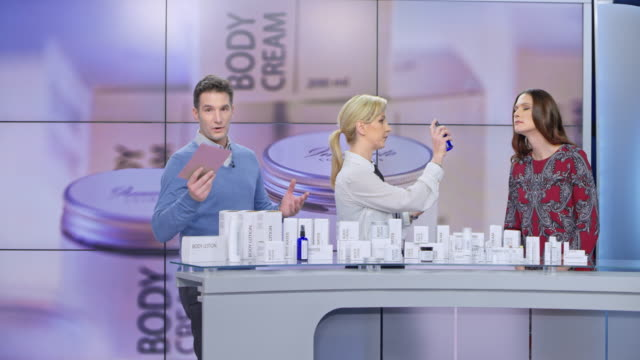 LD Woman presenting a cosmetic line on the tv show spraying some perfume onto the female model while talking to the audience and the male host Wide locked down shot of a female presenter of a cosmetic line on the tv show spraying some perfume onto the female model while talking to the audience and the male host of the show. Shot in Slovenia. television host stock videos & royalty-free footage