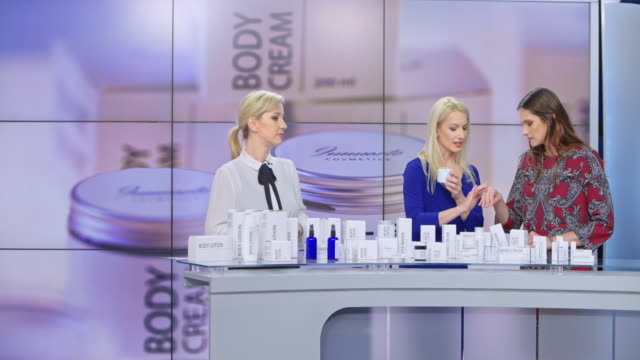 LD Woman presenting a cream from her cosmetic line rubbing some on the female model's hand while the female tv show host is talking Wide locked down shot of a female cosmetic line presenter rubbing some cream on the female model's hand while the female tv show host talks about the products. Shot in Slovenia. television host stock videos & royalty-free footage