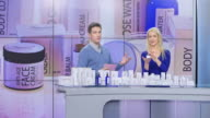 istock LD Woman presenting cosmetic products on the infomercial hosted by a male host 986262578