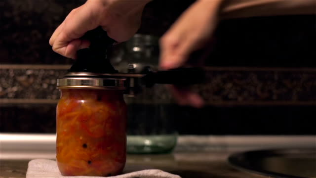 vídeos de stock e filmes b-roll de woman preserves vegetables using seaming key - jam jar