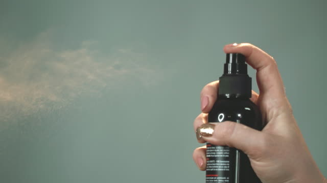 Woman presses a button on bottle, from which varnish or a fixing fluid splashes.
