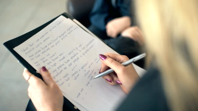 Woman psychologist making notes during therapy session with boy video