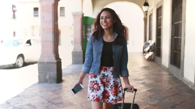 woman pulling a suitcase - turysta filmów i materiałów b-roll