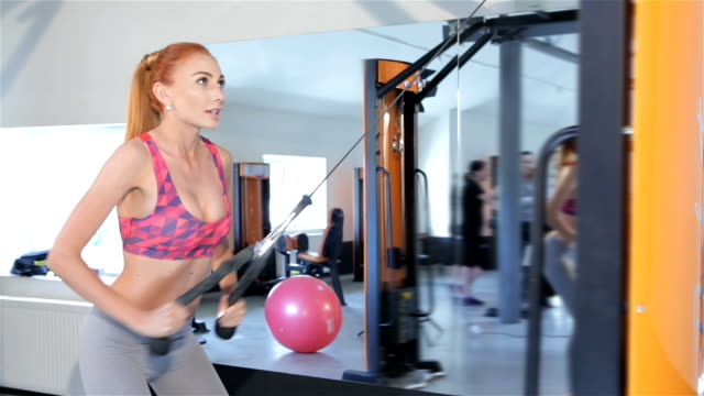 Woman pulling the rope of gym machine to her thighs at the fitness centre video