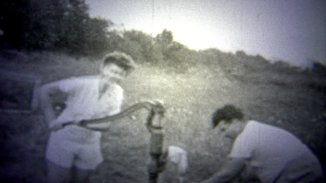 OKLAHOMA, USA - 1943: A woman pumping the well while a man washes. video
