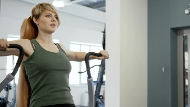 Woman pumps her back muscles Young woman wearing sporty outfit is in the gym. Sporty young smiling woman sits at the training apparatus. Woman actively makes exercises for her back muscles. Young female makes an effort and breathes. human back stock videos & royalty-free footage