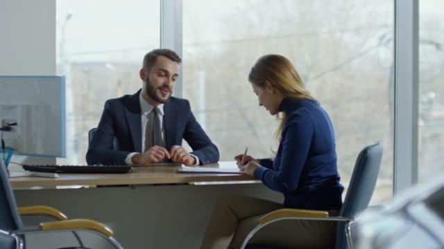 Woman Purchasing Car at Dealership PAN of cheerful auto salesman in suit sitting at his desk and talking with happy female client signing purchase agreement, then giving her keys from new car and shaking hands salesman stock videos & royalty-free footage