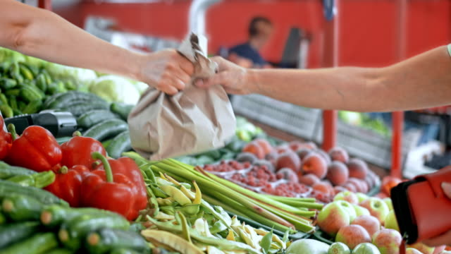PAN Woman purchasing produce at the marketplace Medium panning shot of a female customer paying for produce with cash at the marketplace and the female farmer is handing her a brown bag with groceries. giving stock videos & royalty-free footage