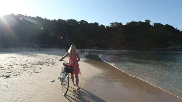 Woman pushes bicycle along tropical beach video