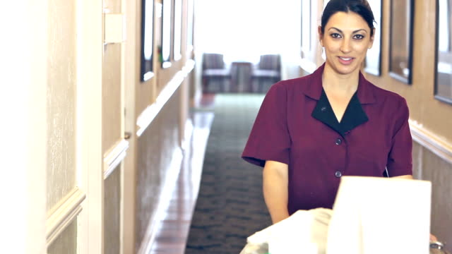 donna spingendo carrello pulizia verso il basso corridoio - addetto alle pulizie video stock e b–roll