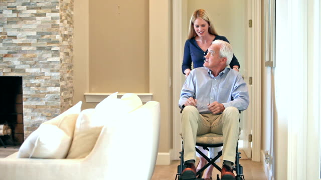 Woman pushing senior man in wheelchair at home