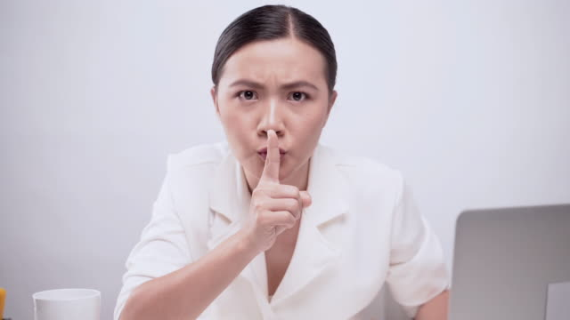 Woman put finger on her lip over white background