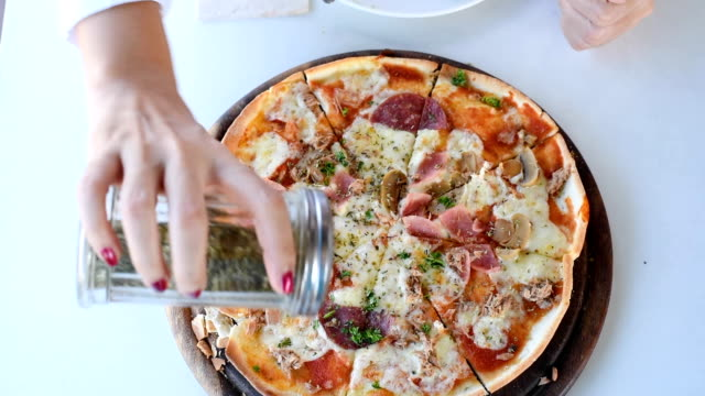 Woman put oregano on Pizza video