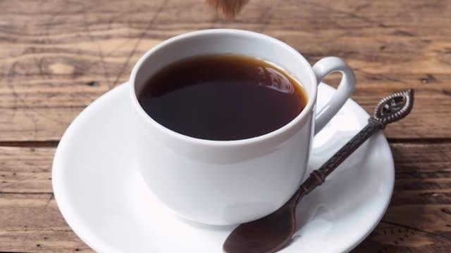 la donna mette un pezzo di zucchero di canna in una tazza di caffè espresso nero. sfondo in legno. primo tempo - lattaio video stock e b–roll
