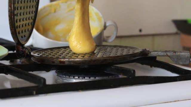 a woman puts dough on a hot waffle iron. - płyta do pieczenia filmów i materiałów b-roll