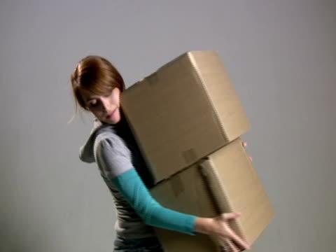 stockvideo's en b-roll-footage met woman puts down boxes - minder dan 10 seconden