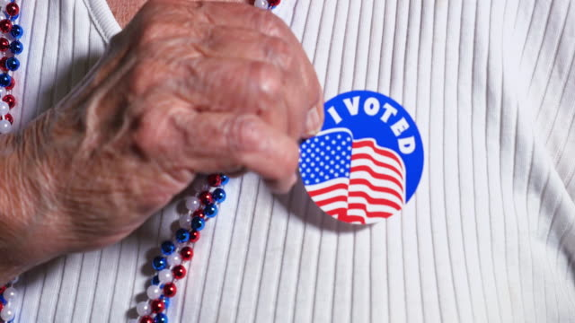 Woman Puts I Voted Sticker on Blouse An elderly woman puts an I Voted sticker on her shirt. vote stock videos & royalty-free footage