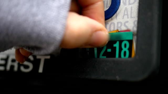 woman puts new expiration date sticker on license plate - talerz filmów i materiałów b-roll