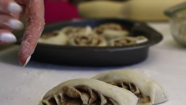 a woman puts on a baking sheet dough pieces for cinnabon. close-up shot. - formare pane video stock e b–roll
