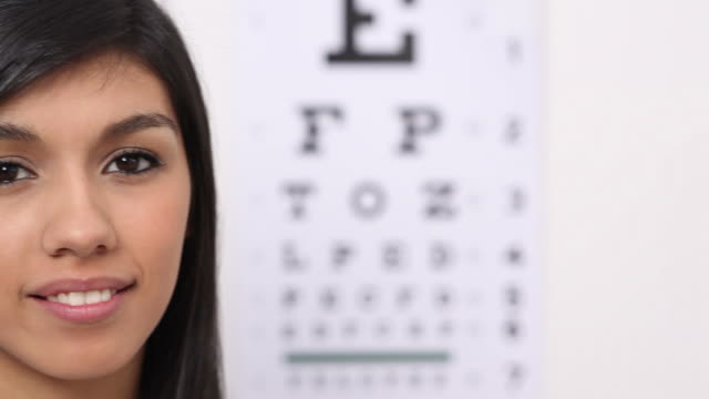 woman puts on glasses - optometrist stock videos and b-roll footage