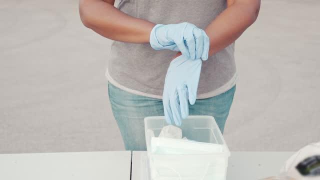 vídeos y material grabado en eventos de stock de la mujer se pone guantes de protección antes de ser voluntaria durante la conducción de alimentos - food drive