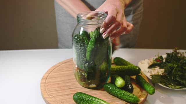 Woman puts spices and fresh cucumbers in a glass jar, preparing for canning Woman puts spices and fresh cucumbers in a glass jar for homemade canning pickle stock videos & royalty-free footage