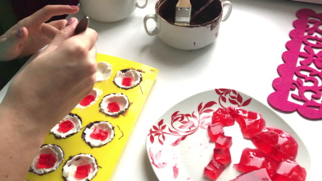 A woman puts strawberry jelly on a curd in silicone mold. The mold is smeared with melted white and dark chocolate. Nearby strawberry jelly on a plate. A woman puts strawberry jelly on a curd in silicone mold. The mold is smeared with melted white and dark chocolate. Nearby strawberry jelly on a plate. stuffed stock videos & royalty-free footage