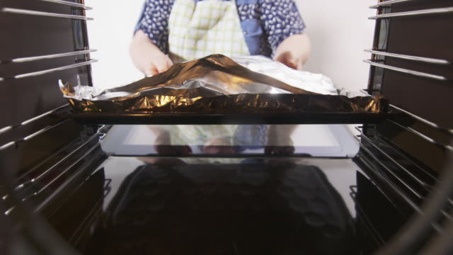 Woman puts the baking sheet covered with aluminum foil in a preheated oven video