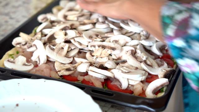 Una mujer pone los ingredientes en la masa para cocinar pizza. Cerca de las manos - vídeo