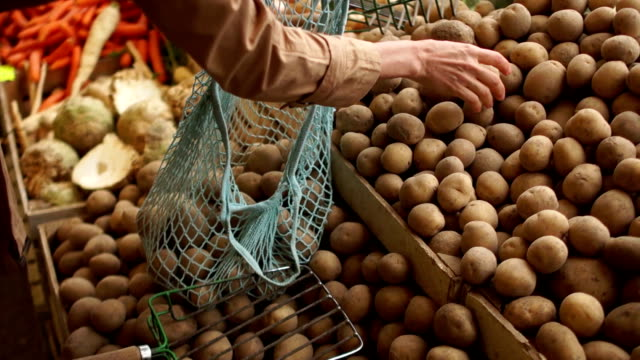 woman puts their hands in a string bag new potatoes from wooden boxes on the market. - patate video stock e b–roll