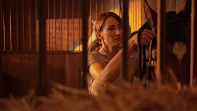 SLO, dans le Missouri, DS Femme faisant une bride sur le cheval - Vidéo