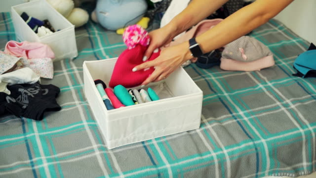 Woman Putting Baby Clothes into a Box