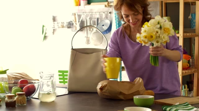 Woman putting beautiful bouquet of daffodils in a vase on her kitchen counter