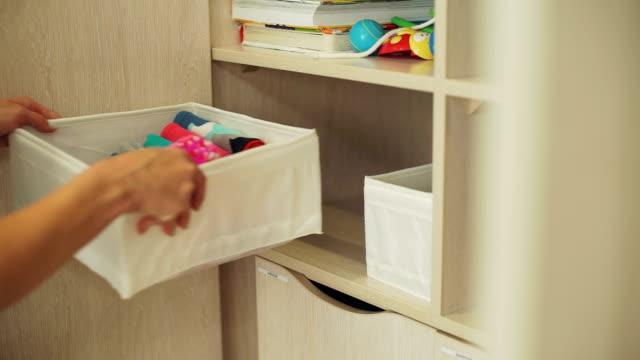 vídeos y material grabado en eventos de stock de mujer putting box con ropa de bebé en un armario - desordenado
